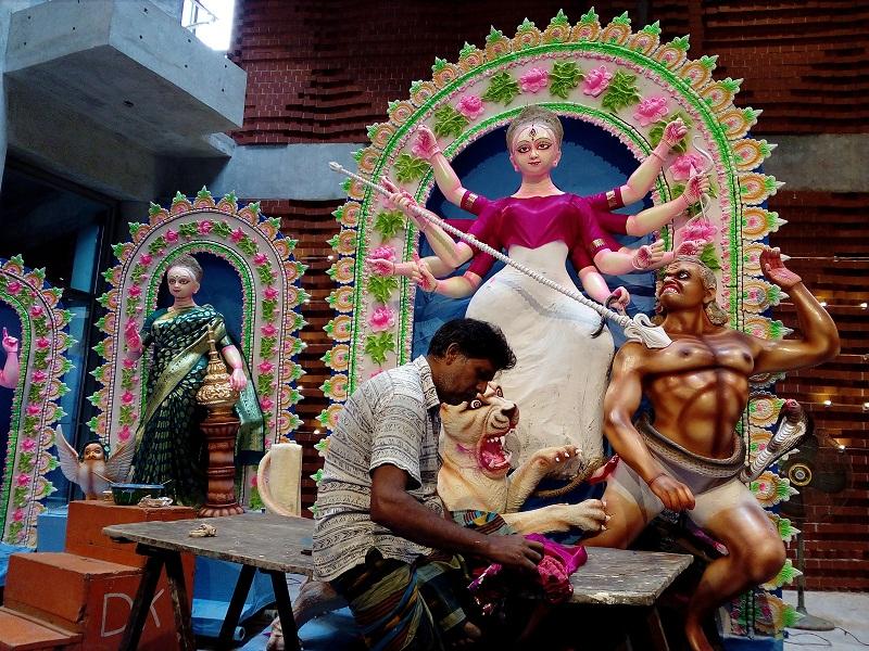 ঢাকেশ্বরী মন্দিরে দেবী দূরগাকে পরানোর জন্য শাড়ির ভাঁজ ঠিক করছেন প্রতিমাশিল্পী